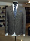 Stylish business suit on a mannequin. Grey jacket with shirt and a blue  tie in a male clothing shop Stock Photography