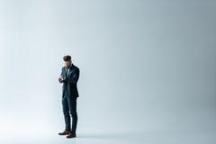 Stylish businessman checking wristwatch on grey Stock Images
