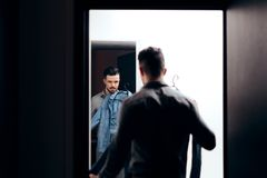 Stylish  Man Checking Himself in the Mirror Trying on Clothes stock image