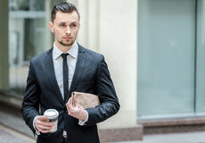 Stylish businessman holding a business newspaper and looking awa Stock Image