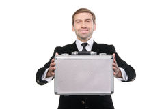 Stylish businessman presenting a metal suitcase. Royalty Free Stock Photos