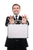 Stylish businessman presenting a metal suitcase. Royalty Free Stock Photo