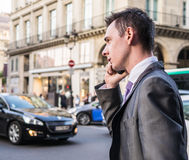 Stylish businessman takes cell phone call on Paris street Stock Photos