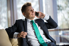 Stylish businessman talking to someone on the Stock Images