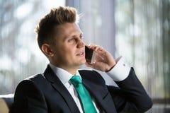Stylish businessman talking to someone on the Royalty Free Stock Photo