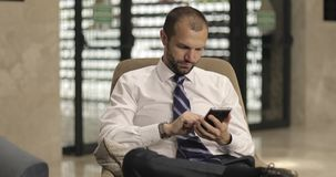 A stylish businessman uses a mobile phone sitting in the hotel lobby or office. A bearded man in a white shirt and tie is typing a message on the tablet at the stock footage