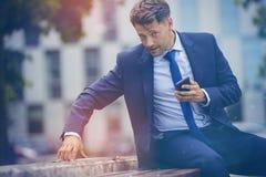 Stylish businessman using digital tablet on retaining wall Stock Images