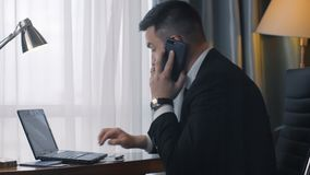 Stylish businessman using phone and laptop. Side close up view of confident man in suit sitting at table in hotel room working on laptop and having business call stock video