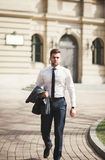 Stylish businessman walking outdoors and looking away Stock Image