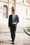 Stylish businessman walking outdoors and looking away Stock Photo