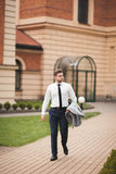 Stylish businessman walking outdoors and looking away Royalty Free Stock Photos