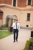 Stylish businessman walking outdoors and looking away Royalty Free Stock Images