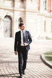 Stylish businessman walking outdoors and looking away Royalty Free Stock Image