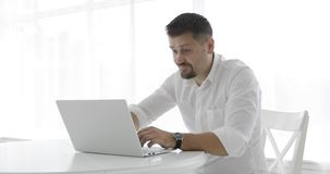 Stylish businessman in a white shirt nervously typing on a laptop and closing it. A young man takes a mobile and leaves. Modern room with white furniture. 4K stock footage