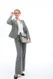 Stylish businesswoman adjusting her glasses. Stylish businesswoman in an elegant grey suit standing adjusting her glasses and holding a folio, full length Royalty Free Stock Images