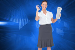 Stylish businesswoman making gesture while holding newspaper Royalty Free Stock Images
