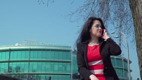 Stylish businesswoman in red dress talk on phone at business center background. Beautiful elegant woman wearing red dress is talking on phone at business center stock video footage