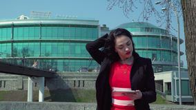 Stylish businesswoman in red dress using digital tablet outdoors. Beautiful elegant woman wearing red dress using herdigital tablet at office center background stock video footage