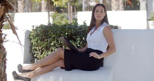 Stylish businesswoman relaxing in a park stock footage
