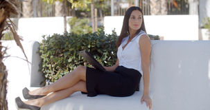 Stylish businesswoman relaxing in a park Stock Photography
