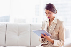 Stylish businesswoman sitting on sofa using tablet pc Stock Photography