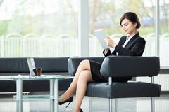 Stylish businesswoman sitting on sofa using tablet pc in the office. stock photo