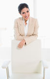Stylish businesswoman standing behind her chair Royalty Free Stock Photos