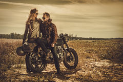 Stylish cafe racer couple on the vintage custom motorcycles in a field. Royalty Free Stock Image