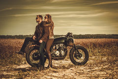 Stylish cafe racer couple on the vintage custom motorcycles in a field. royalty free stock photos