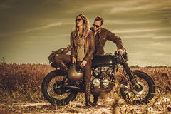 Stylish cafe racer couple on the vintage custom motorcycles in a field. Stock Photos