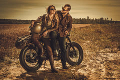 Stylish cafe racer couple on the vintage custom motorcycles in a field. Young, stylish cafe racer couple on the vintage custom motorcycles in a field Stock Image