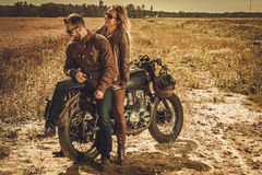 Stylish cafe racer couple on the vintage custom motorcycles in a field. Stock Photo