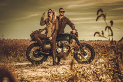 Stylish cafe racer couple on the vintage custom motorcycles in a field. Stock Image