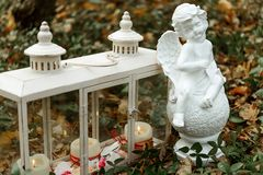 Stylish candles in glass rustic lantern and angel statue, arrangement for wedding ceremony in forest stock photo