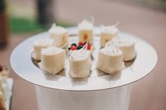 Stylish candy bar with delicious modern mascarpone cakes, cookie. S, in pink and white colors. luxury catering in restaurant. wedding reception. modern sweet stock photography