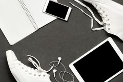 Stylish casual Flat lay Of White Sneakers On black Background with phone, headphones, tablet, copy book Royalty Free Stock Photo