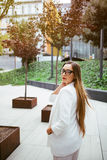 Stylish Caucasian business woman is standing near modern office building. Portrait of business woman walking and smiling outdoor. Woman is going home after work Stock Photos