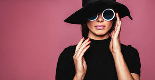 Stylish caucasian female model. Close up portrait of stylish caucasian female model. Beautiful woman in hat and sunglasses posing over pink background stock photography