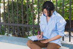 Stylish Caucasian student girl sitting at sidewalk, making notice onher notebook planner for meetings. Young woman with earphone. Listen and preparing for exam stock photos