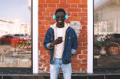 Stylish cheerful african man using smartphone listening to music in wireless headphones on city street over brick wall stock images