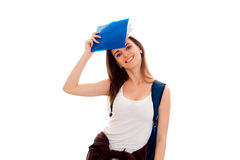 Stylish cheerful brunette student girl with blue backpack and folder for notebooks in her hands looking and smiling on Royalty Free Stock Photo