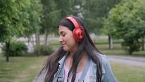 Stylish cheerful girl dancing in the park listening to music on headphones. Stylish cheerful girl in jeans clothes dancing in the park listening to music in red stock video footage