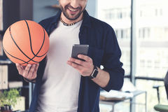 Stylish cheerful guy is using smartphone Royalty Free Stock Images