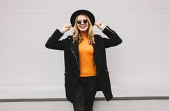 Stylish cheerful smiling young woman having fun in city on gray. Wall background royalty free stock photography