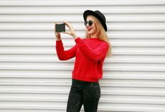 Stylish cheerful woman taking selfie picture by phone in knitted red sweater on white wall. Background stock images