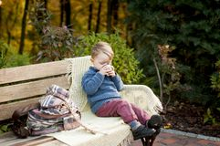 A stylish child boy sits on a bench with a knitted plaid and dri Royalty Free Stock Photos