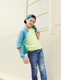 Stylish child boy wearing a shirt and baseball cap. In city Royalty Free Stock Photo