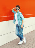 Stylish child boy wearing a sunglasses and shirt in city. Over red background Royalty Free Stock Images