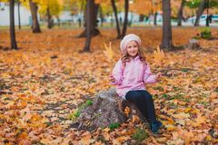 Stylish child girl 5-6 year old wearing trendy pink coat in autumn park. Looking at camera. Autumn season. Childhood. stock photo