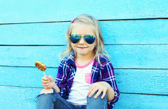 Stylish child with sweet caramel lollipop over colorful blue Royalty Free Stock Photography